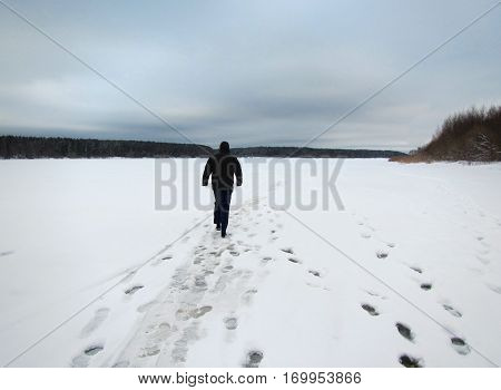 Solitary man walking on snowy frozen river in Russia