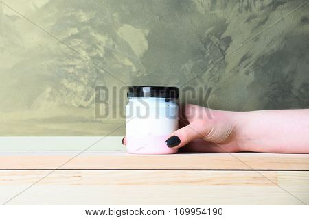 White Jar With Lotion Or Bath Salt In Female Hand
