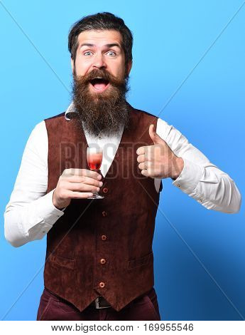 handsome bearded man with long beard and mustache on smiling face tasting glass of alcoholic shot in vintage suede leather waistcoat on blue studio background