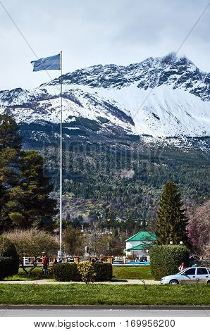 EL BOLSON RIO NEGRO ARGENTINA - SEPTEMBER 10 2015: The argentine flag and a beautiful snowy mountain in the background in El Bolson Rio Negro Argentina.
