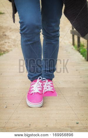 Girl in oink sneakers climbing up the stairs outdoors.