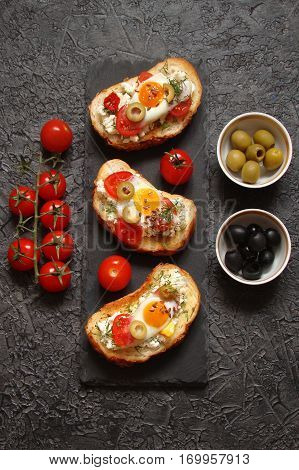 Bruschetta crostini with cream cheese with cherry tomatoes herbs olives capers and fried egg on black background