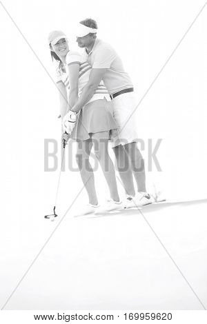 Low angle view of couple playing golf at course against clear sky