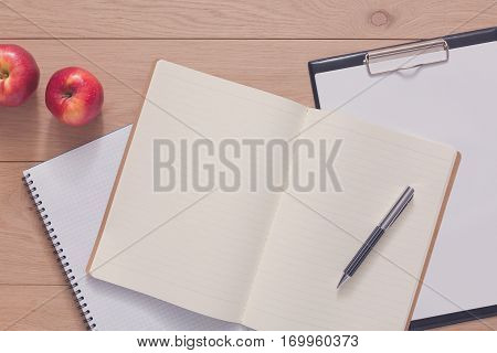 Notepad, diary, note papers and apple fruit. Office or student's devices on modern wooden desk. Working table top view. Education, writing and studying background with copy space on paper sheet