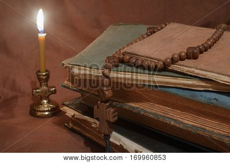 old book by candlelight with cross broun background