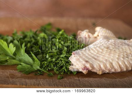 Boiled chicken wing with chopped parsley on a wooden cutting board in kitchen