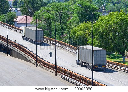 trucks going up the bridge, cargo transportation, delivery and shipping concept, green trees on background