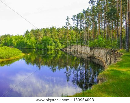 The sandy bank of the river Pra in the forest and blue sky background