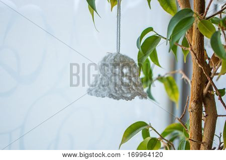 White knitted Christmas bell hanging on a ficus flower