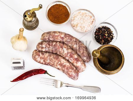 Crude homemade sausage with spices. Studio Photo