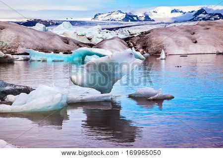 Icebergs and ice floes are reflected in the smooth water surface.  Drift ice Ice Lagoon - Jokulsarlon. Morning in the Ice Lagoon, Iceland.  The concept of extreme northern tourism