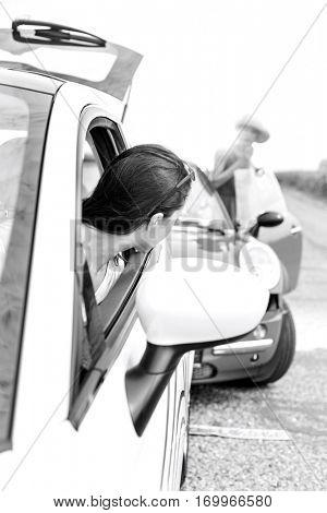 Woman looking at female crashing car on road