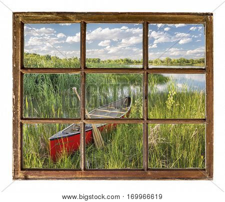red canoe on lake shore in summer scenery as seen  through vintage, grunge, sash window with dirty glass