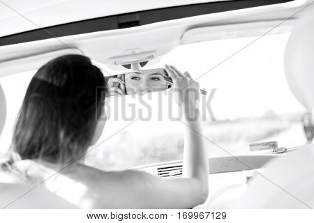 Woman adjusting rearview mirror while using mobile phone in car