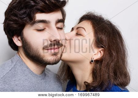 Beautiful couple in love isolated over white background. A girlfriend kissing passionately his stylish boyfriend in chin. A bearded hipster receiving pleasure from his girfriend`s kiss