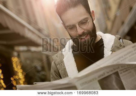 Happy guy eading a newspaper on the street