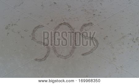 Top view photo of SOS written in sand on tropical beach. Concept photo of help emergency desperation lost and hope