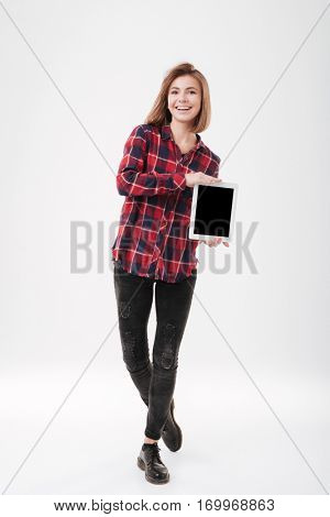 Full length potrait of a smiling young woman in plaid shirt standing and holding blank screen tablet computer over white background