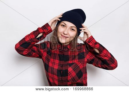 Hipster girl in stylish cap dressed in red checked shirt having happy expression holding her hands on the head isolated over white background. People style and fashion concept