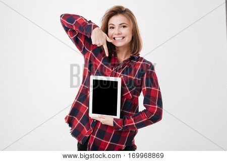 Cheerful cute woman in plaid shirt holding and pointing finger on blank screen tablet over white background