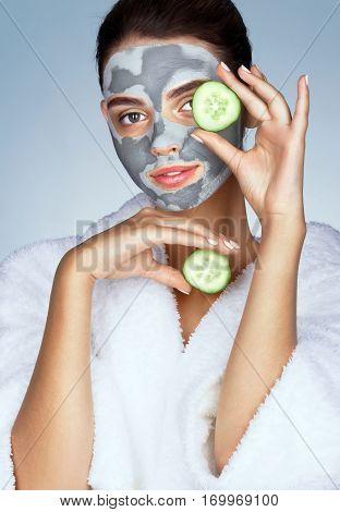 Beautiful girl in white bathrobe and with mask of clay. Photo of brunette woman holding cucumber slices near her face on blue background. Grooming himself