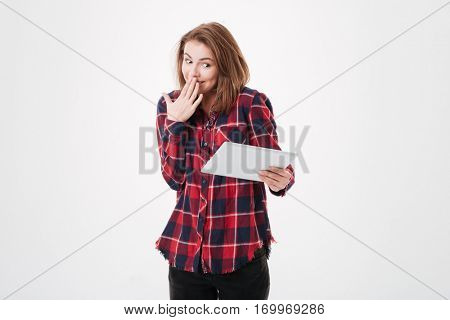 Portrait of a shy young girl in plaid shirt looking at tablet computer and covering her mouth with hand isolated on a white background