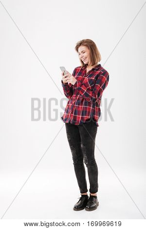Full length portrait of a smiling cheerful woman in plaid shirt standing and using mobile phone over white background