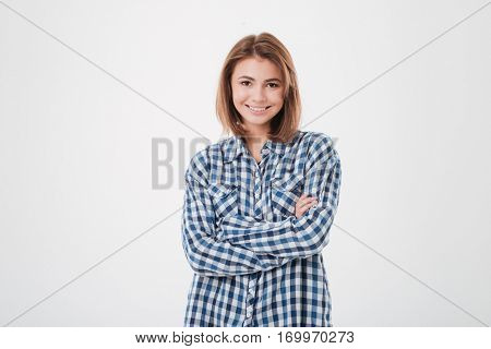 Portrait of a cheerful smiling woman in plaid shirt standing with arms folded isolated on the white background