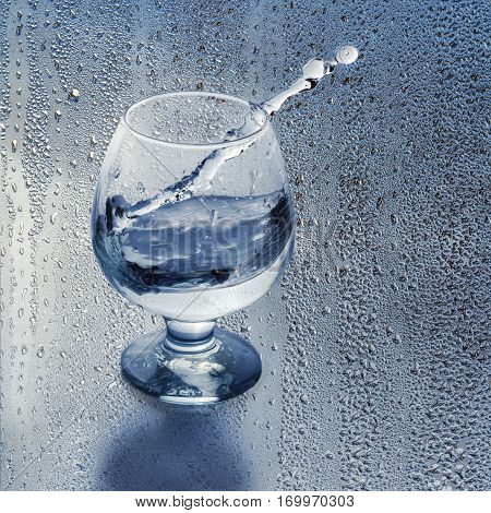 Clean water in a glass and splash on the background of the drops. Cropping into a square, place for text.