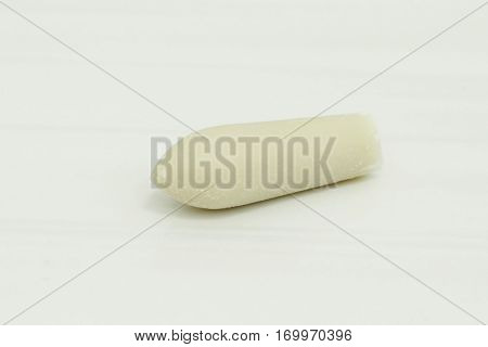 one suppository on white background, shallow depth of field