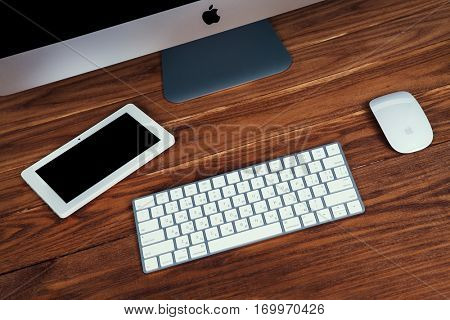 UKRAINE, RIVNE, December 2, 2016. Apple Computer iMac 27 retina display 5K keyboard and magic mouse on wood table.