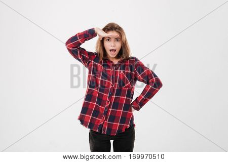 Portrait of beautiful young woman in plaid shirt looking far away isolated on a white background