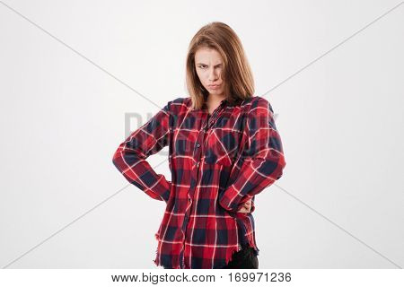 Offended upset woman in plaid shirt standing with hands oh hips isolated on a white background