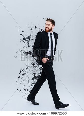 Full length portrait of a smiling bearded businessman in black suit walking and looking away with special effects