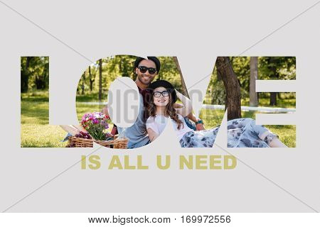 Relaxed young smiling couple in love having picnic at the park,all you need is love signature