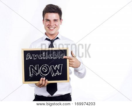 Available Now - Young Smiling Businessman Holding Chalkboard With Text