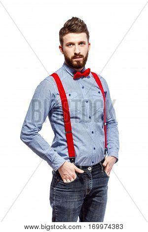 stylish guy wearing blue shirt, red bowtie and suspenders isolated on white. smile. stand. hands in the pocket.