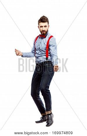 stylish guy in the blue shirt with red bowtie and suspenders isolated on white. dancing, clicking fingers.