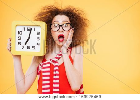 Surprised bright model in glasses with clock in hand and one hand holding on cheek. Isolated orange background