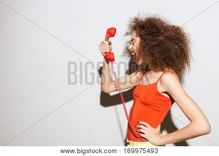 Side view of Unusual model screaming at handset with arm at hip. Isolated gray background