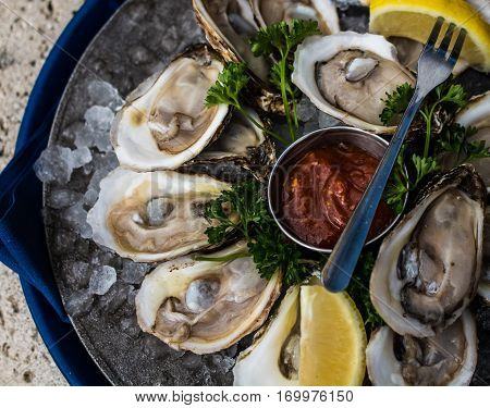 A platter of Raspberry Point Oysters from Prince Edward Island, Canada, served on ice with lemon and cocktail sauce