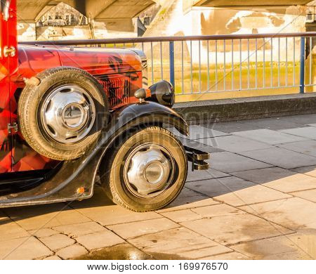 front of the old style car on the banks of the river color car