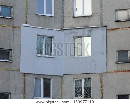 A fragment of a multi-storey concrete panel residential building with an externally applied external insulation on the facade of the apartment.