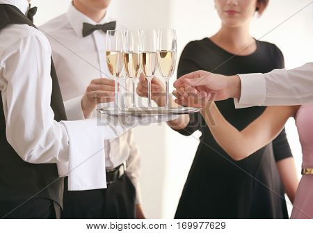 Waiter in uniform serving champagne during buffet catering party