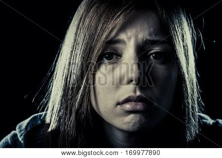 lonely young teenager girl or woman in stress and pain suffering depression looking sad and scared with fear face expression isolated on black background victim of abuse or in mental condition