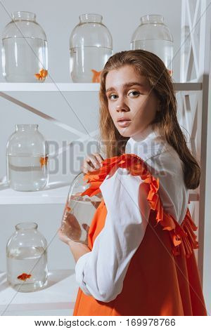 Charming young woman standing near the closet with gold fishes in jars on shelves