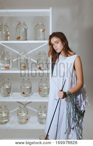 Attractive young woman holding fishing rod and net standing near gold fishes in jars