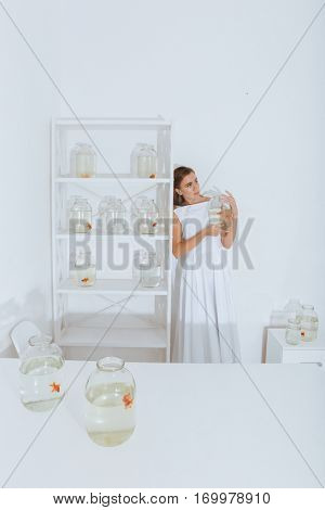 Cute young woman standing in the room and holding gold fish in jar