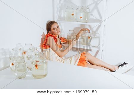 Cute young woman sitting and resting near closet with gold fishes in jars