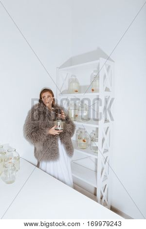 Attractive young woman in fur coat holding gold fish in jar in the room